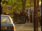 Man Arrested LIB ENGLAND London Feltham shaky camera GV Armed police putting on body armour outside flat where gunman is hiding