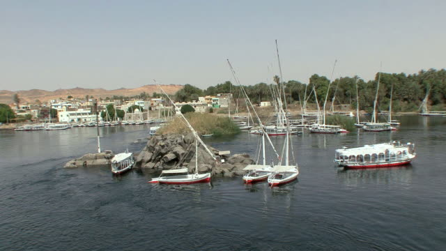 WS Feluccas docked on rocky island, harbor of Aswan, Egypt