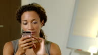 Female African American business executive operates her smartphone.