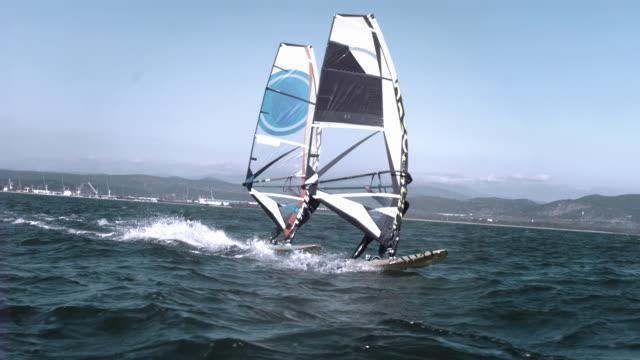 Female and male windsurfer windsurfing