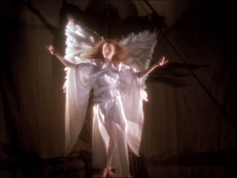 Female angel standing with arms out / wind blows her backward