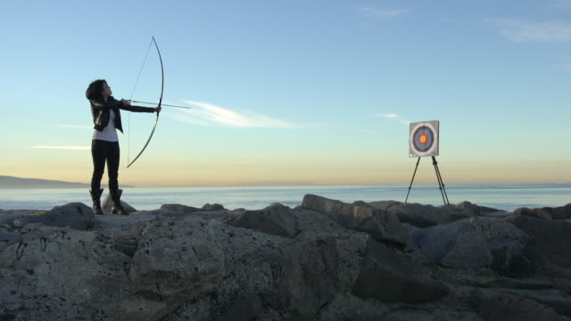 A female archer shooting targets with her bow and arrow.  - Slow Motion