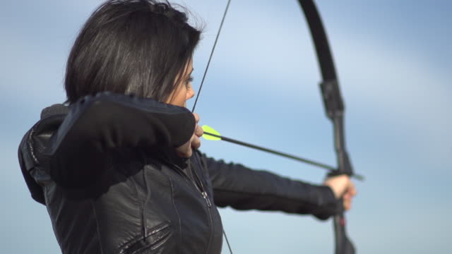 A female archer shooting targets with her bow and arrow.  - Super Slow Motion - filmed at 240 fps