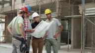 Female architect, a foreman and two construction workers looking at the plan outside at the construction site and pointing at the building to check the progress