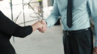 Female architect and male project manager shaking hands at the construction site