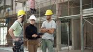 Architektin und zwei Bauarbeiter, die Überprüfung des Plans auf die digitale Tafel außen und zeigt auf das Gebäude, den Fortschritt zu überprüfen