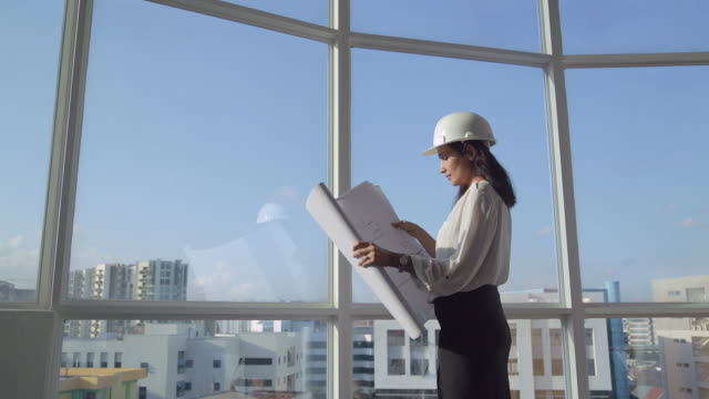 MS SELECTIVE FOCUS Female architect stands at window holding building plans / Singapore