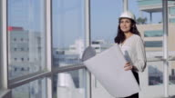 MS SELECTIVE FOCUS Female Architect stands in office with open building plans in her hands / Singapore