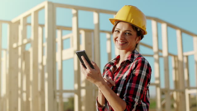 Female architect talking on the phone at construction site