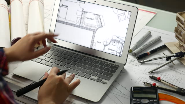 Female Architect Working on Computer with Architectural Model