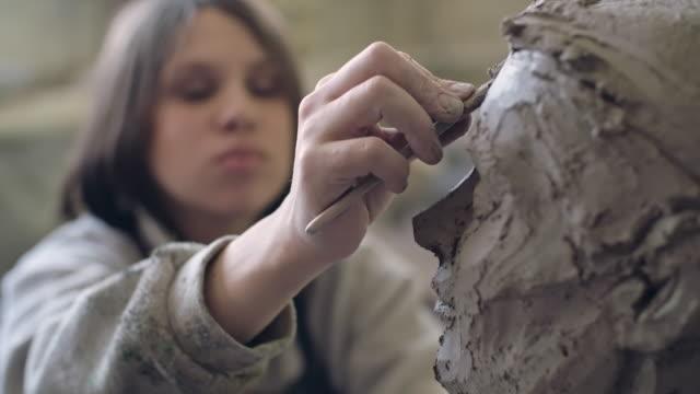 Female artist making a clay head sculpture