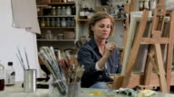 A female artist oil painting at an easel