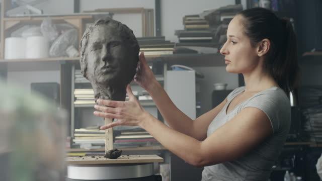 Female artist sculpting face