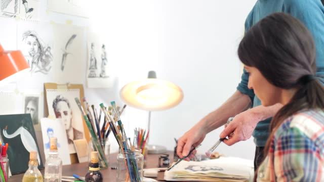 Weibliche Künstler arbeiten mit Ihrem Lehrer im der Werkstatt.
