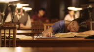 DS vrouwelijke Aziatische vrouw inslapen over boeken in de bibliotheek