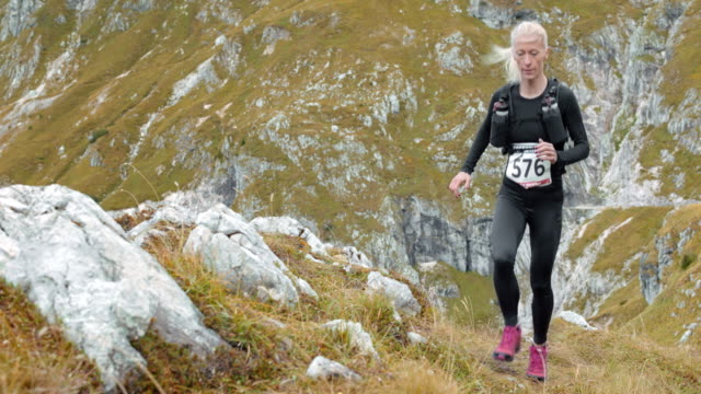 SLO MO Female athlete running a mountain marathon up a grassy slope