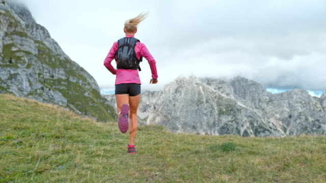 SLO MO Female athlete running across a meadow high in the mountains