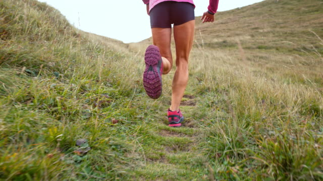 SLO MO Female athlete running on a grassy trail across a meadow