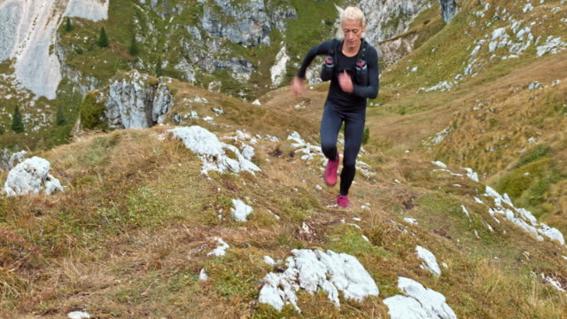Female athlete running on a grassy trail up a mountainside