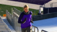 MS Female athlete training in empty stadium running stairs