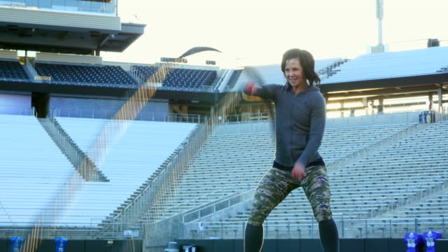 MS Female athlete working out with battle rope exercise during training session on field in stadium