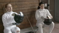 Female athletes putting on fencing equipment