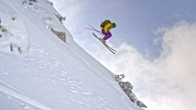 SLO MO Female backcountry skier jumping in powder snow
