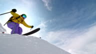 SLO MO Female backcountry skier jumping off a rock