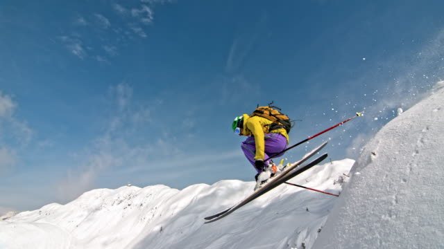 SLO MO Female backcountry skier jumping on sunny mountain slope