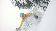 SLO MO Female backcountry skier jumping over the camera