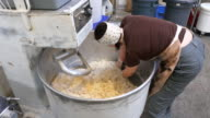 MS Female baker mixing dough in commercial mixer in bakery