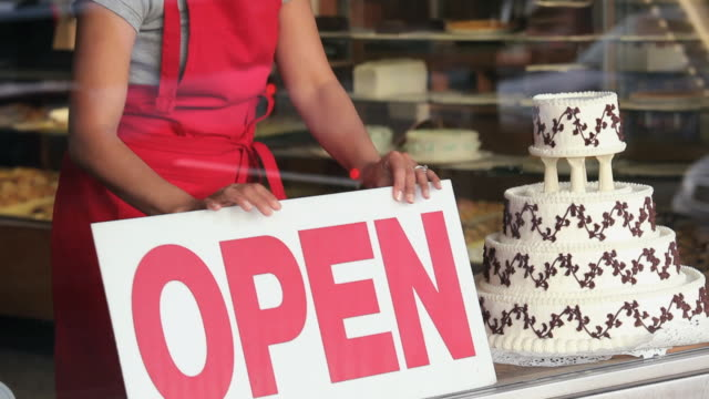 MS TU Female baker placing 'open' sign in bakery's window / Richmond, Virginia, USA