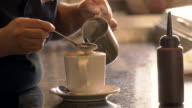 Female barista spoons steaming foam into latte/cappuccino, TU