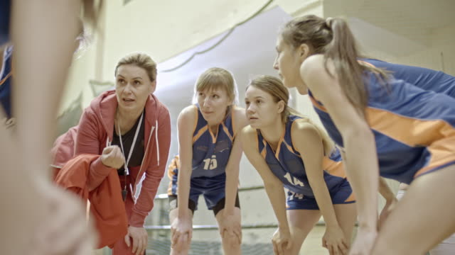 Female basketball players standing in circle and listening instructions from coach
