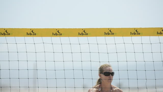 CU of female beach volleyball players spiking and blocking at the net.