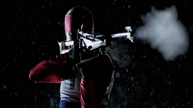 SLO MO female biathlon athlete doing standing shot at night