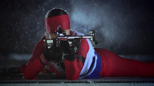 SLO MO female biathlon athlete shooting in prone position