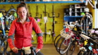 MS PAN Female bicycle shop owner sitting on bicycle her tablet / Santa Fe, New Mexico, United States
