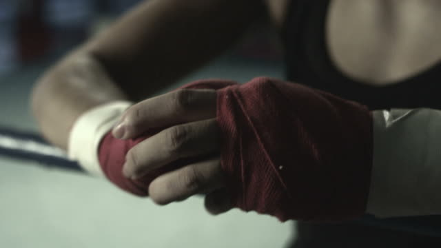 Female boxer wearing hand wraps, camera tilts to show her looking determined