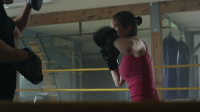 Eine Boxerin, die Arbeit mit einem Trainer an Box-gym