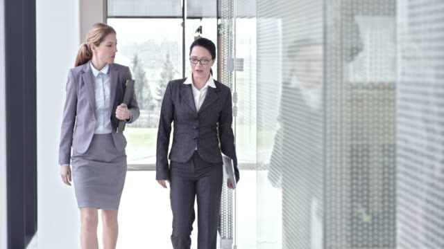 SLO MO Female business colleagues talking and walking in hallway