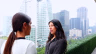 MS SWISH PAN Female business executives standing in discussion on office terrace overlooking city