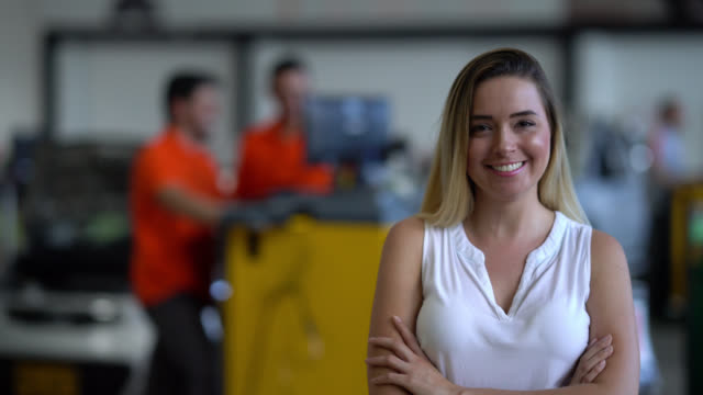 Female business owner of an auto repair shop looking at the camera smiling