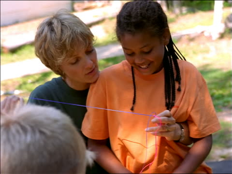 Female camp counselor showing Black girl sitting in her lap how to do craft