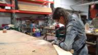 Female carpenter cutting wood in a workshop