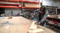 Female carpenter cutting wood