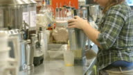 female coffee house employee pours frozen drink from blender into clear plastic serving cup / Redlands, California, USA