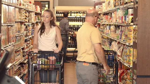 MS female college student with shopping cart in grocery store aisle buying cereal while elderly man pushes shopping cart to the next aisle