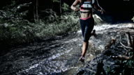 SLO MO DS Female competitor running on a muddy trail at night