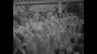 Female contestants parade in line approaching camera wearing bathing suits with sashes bearing the names of their sponsors during local outdoor...